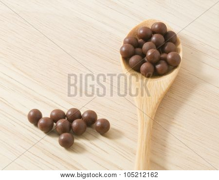 Wooden Spoon Full Of Herbal Cough Lozenges On Cutting Board