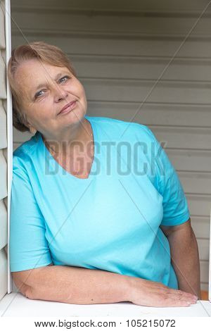 Calm and peaceful pensioner woman at window in dacha