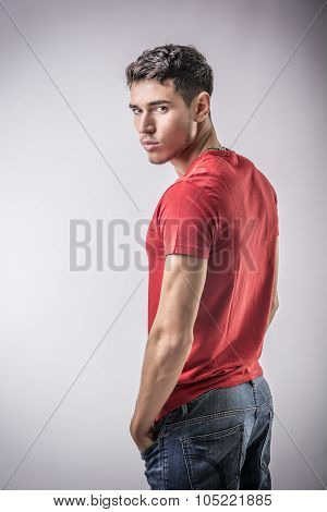 Serious young man looking at camera on light background