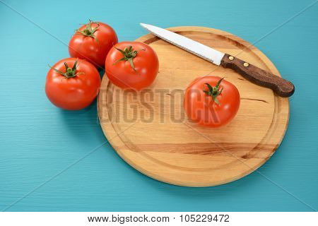 Tomatoes With A Serrated Knife On A Wooden Board