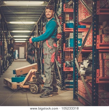 Loader using hand pallet truck in a warehouse