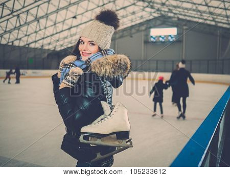 Cheerful girl with skates on ice skating rink
