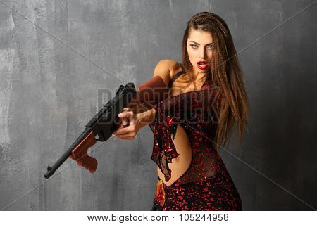 Portrait of evil woman with long hair in open red costume with gun