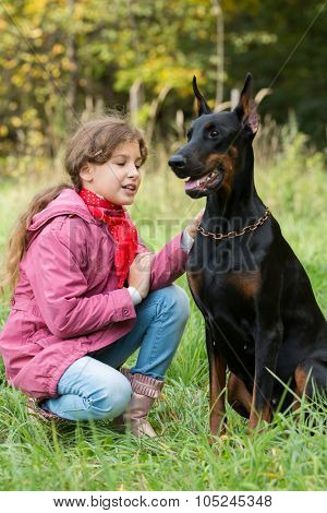 Little girl is sitting on the grass near a dobermann.