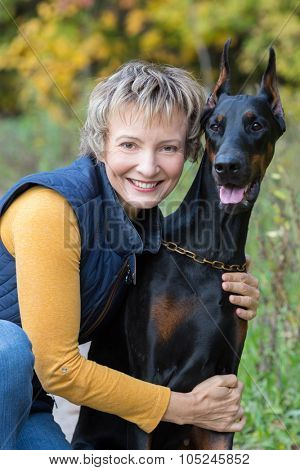 Smiling woman at jacket is hugging the dobermann in a park.
