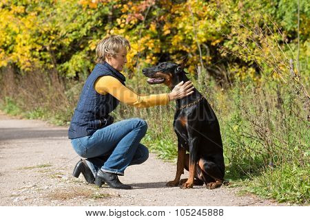 Woman at beige polo-neck is sitting in front of the black dog in a park.