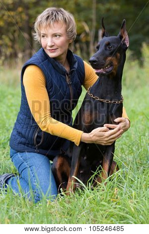 Woman with serious glance is sitting on the lap and hugging a dobermann in park.