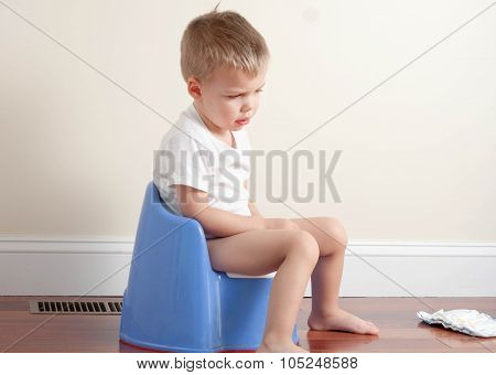sad toddler boy wearing a white t-shirt sitting on a potty