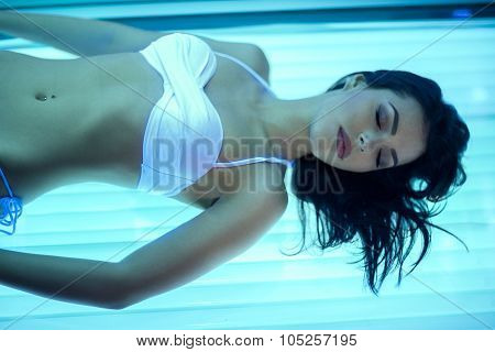 Young woman relaxing in solarium, have tanning skin treatment in bed solarium