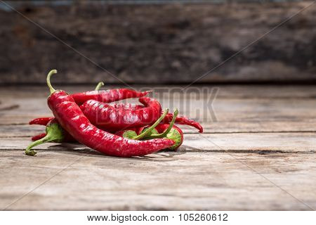 Pile Of Red Chilli Peppers On Wooden Background