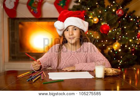 Cute Girl Waiting For Santa With Milk And Cookies At Living Room