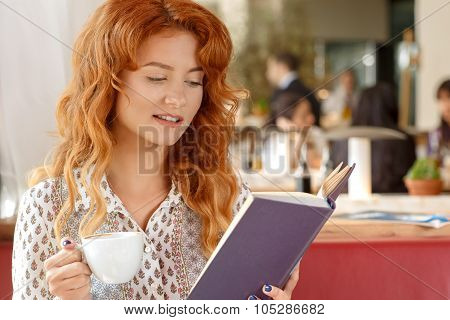 Beautiful red haired girl on coffee break