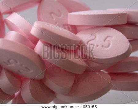 poster of a pile of pink pain pills close up.