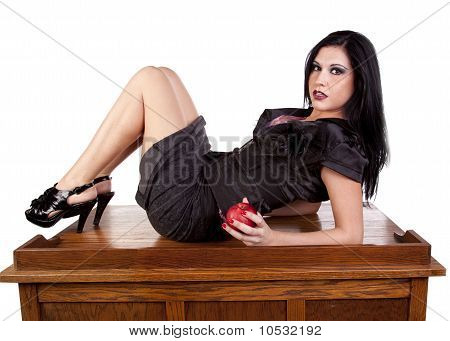 Teacher Laying Back On Desk