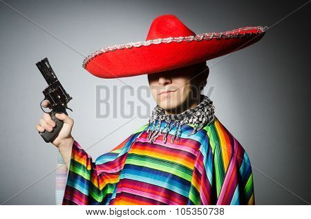 Man in vivid mexican poncho holding handgun against gray poster
