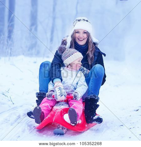 Young happy mother and cute little toddler daughter having fun on a sledge with riding in a winter forest or park. Active leisure with kids in winter on cold snowy days poster