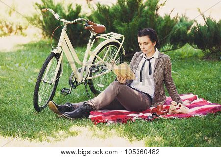 Young Woman With Bicycle Having Picnic In The Park