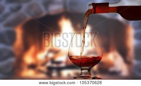 Pouring rred wine in front of fireplace
