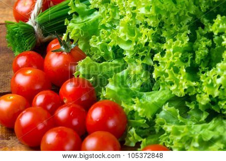 lettuce salad, tomatoes and chives on wooden background.