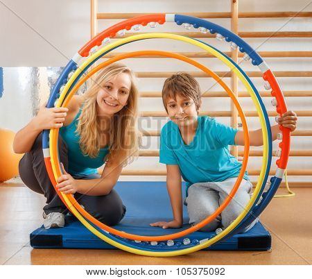 Happy, sports family, mother and son looking through hula hoops