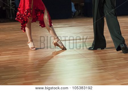 Closeup Of Legs Of Two Professional Dancers Performing Latin -american Program On Dancefloor
