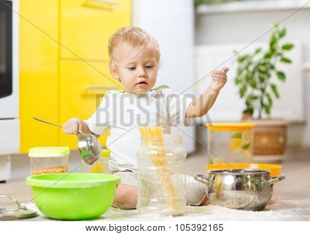 Little boy playing with kitchenware and foodstuffs in kitchen