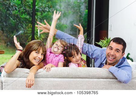 Beautiful hispanic family of four posing with heads sticking up from back of sofa looking at camera smiling. poster