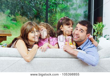Beautiful hispanic family of four posing with heads sticking up from back sofa looking at camera smi