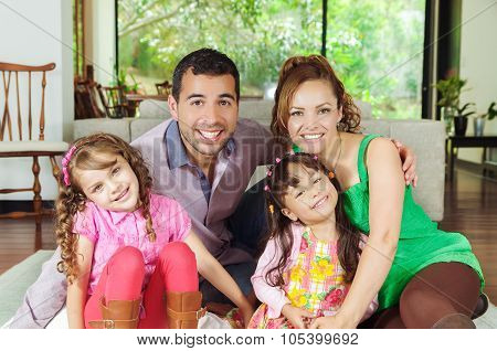 Beautiful hispanic family of four sitting on floor in livingroom posing happily for camera