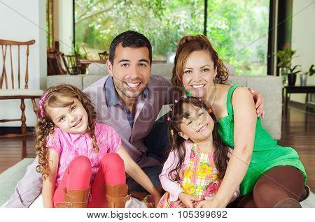 Beautiful hispanic family of four sitting on floor in livingroom posing happily for camera