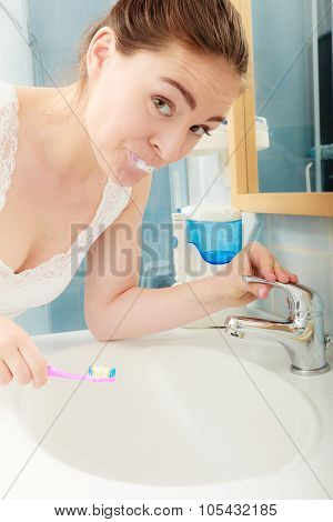 Young woman brushing cleaning teeth. Girl with toothbrush in bathroom. Oral hygiene. poster