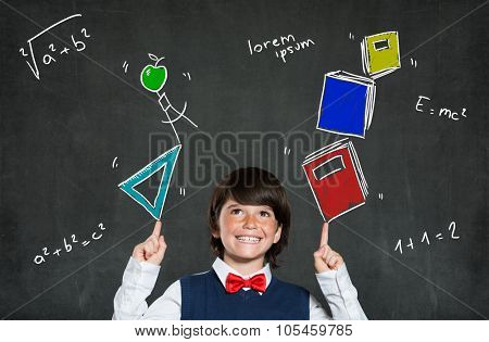 Little boy playing with books and school instruments. Portrait of happy boy smiling and looking up. Cheerful cute child indicates formulas with arms raised above the head. Education concept.