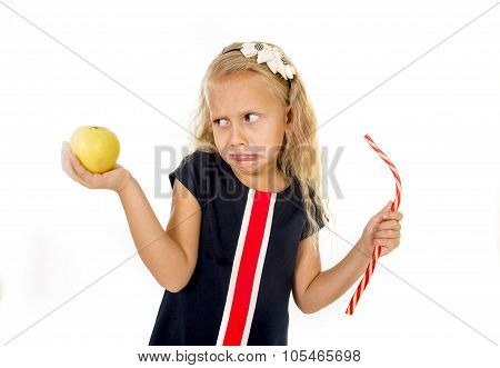 little beautiful female child with blond hair choosing dessert holding unhealthy but tasty red candy licorice and apple fruit in healthy versus unhealthy die nutrition isolated on white background poster