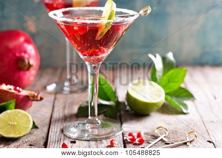 Pomegranate martini with slices of lime and pomegranate seeds poster