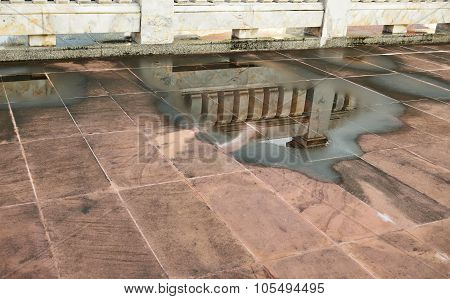 Reflection Of Marble Wall In Water Logged