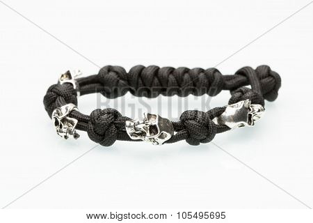 Black braided bracelet with skulls on white background.  synthetic cord poster