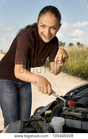 Inexperienced young woman with lug wrench in her hands tries to repair her broken car.