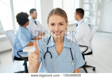 health care, gesture, profession, people and medicine concept - happy female doctor or nurse over group of medics meeting at hospital showing thumbs up gesture poster