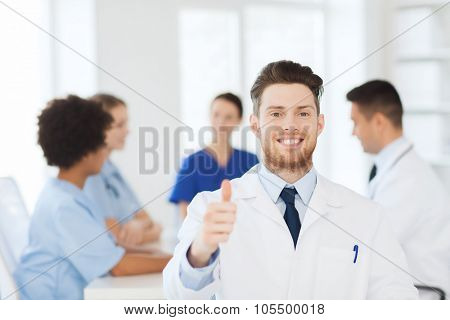 clinic, profession, people and medicine concept - happy male doctor over group of medics meeting at hospital showing thumbs up gesture poster
