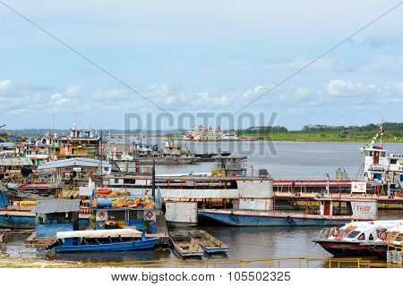 IQUITOS, PERU - OCTOBER 11, 2015: Boats at dock in the Itaya River. Iquitos is the largest metropolis in the Peruvian Amazon, and the sixth most populous city of Peru.