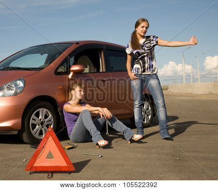 Two young women on the road: one of them is trying to stop a car and another sad girl is sitting on the road.