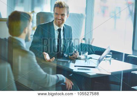 Happy employee discussing idea to colleague in office