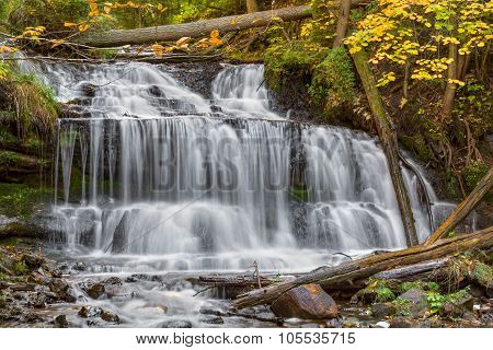 Wagner Falls a beautiful waterfall in Alger County of Michigan's Upper Peninsula pours over rock ledges in early autumn. poster