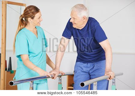 Old man exercising with physiotherapist on a horizontal bar