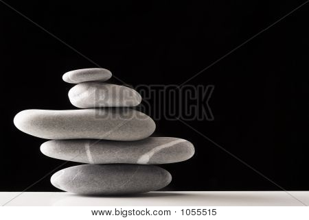 five stones pile over black on a white table poster