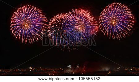 Fireworks. Colorful violet fireworks in Malta, dark sky background and house light in the far, Malta