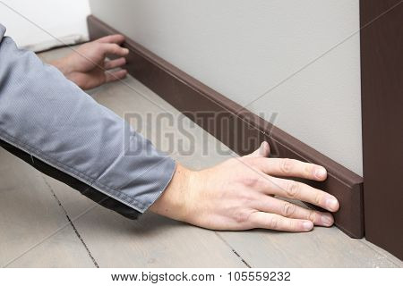 Installation Of A Brown Wooden Baseboard At The Bottom Of The Wall
