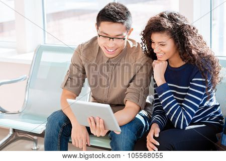 Asian boy in black glasses and african american curly girl girl are using tablet computer