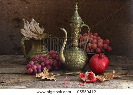 Wine in a copper jug submitted with grapes and a juicy pomegranate poster