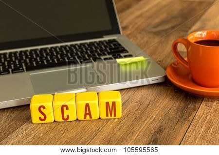 Scam written on a wooden cube in front of a laptop